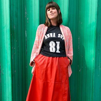 Caroline Jones poses against green door wearing a red leather skirt