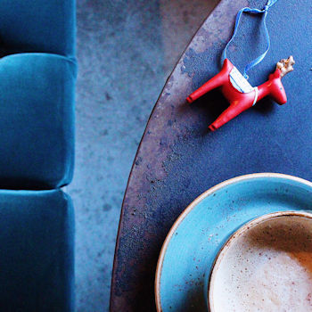 Coffee cup pictured from above on a table next to a green velvet bench