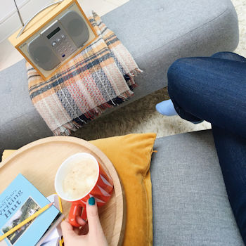 Writer Helen Perry seated on sofa with coffee and digital radio