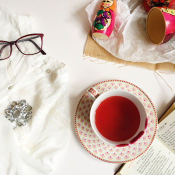 A flat lay by Helen Perry featuring a pink cup and saucer and Russian dolls