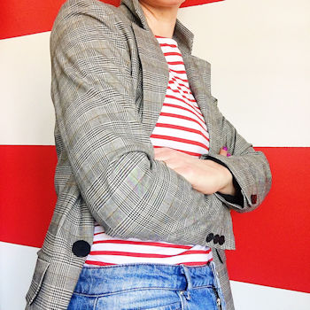 Helen Perry in jeans, a red Breton top and jeans against a red and white striped wall. Instagram post.