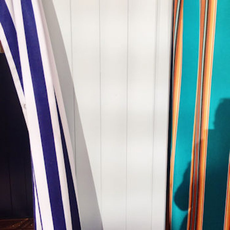 Two striped, colourful cubicle curtains