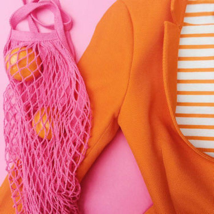 orange coat, pink string bag, oranges